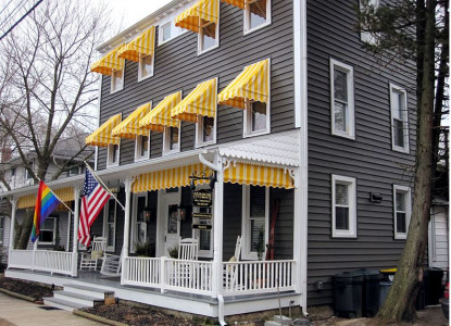 The Rehoboth Guest House Outside front porch pride flag american flag