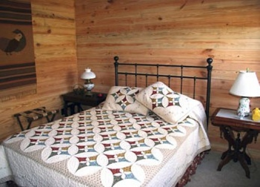 The bedroom features a King size bed with handmade quilt.