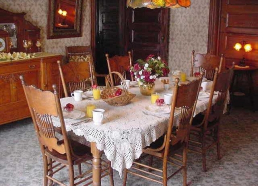 Antique furniture fills the dining room with the ambiance of a bygone era