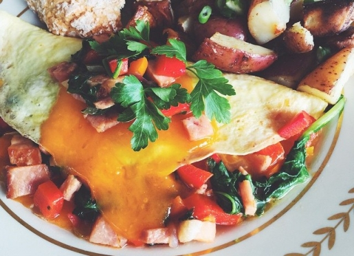 Breakfast omelette with ham, spinach, arugula, and local vegetables.