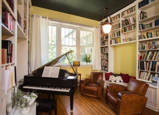 The Sweet Biscuit Inn landing with grand piano and ceiling-high library