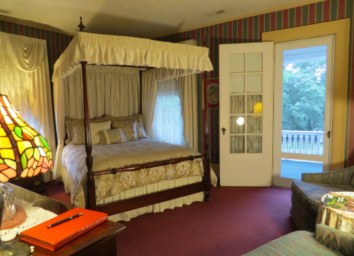 Lady Anne room with canopy bed, private patio overlooking gardens, and sitting area in room.